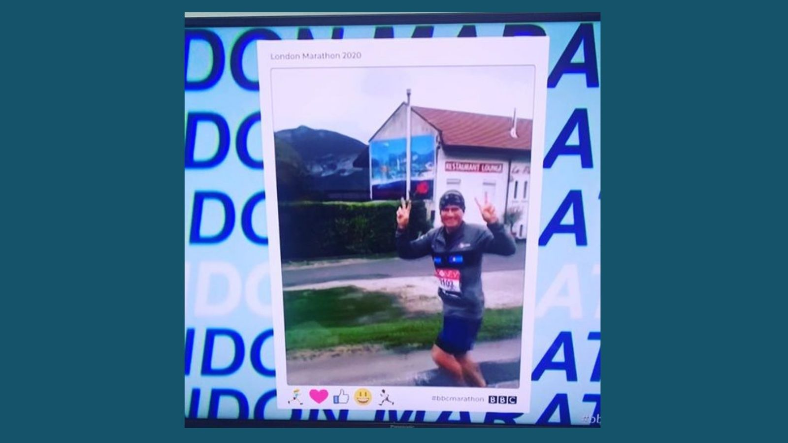 picture of Mark as seen on BBC coverage, jogging make a peace sign and smiling