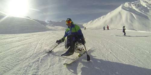 A sit skier enjoying adaptive skiing